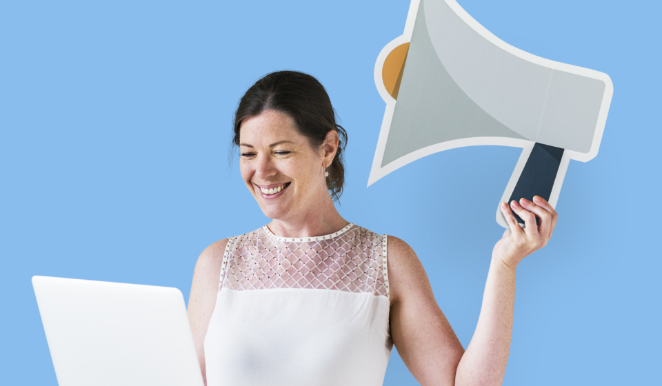 Woman holding a megaphone icon and using a laptop